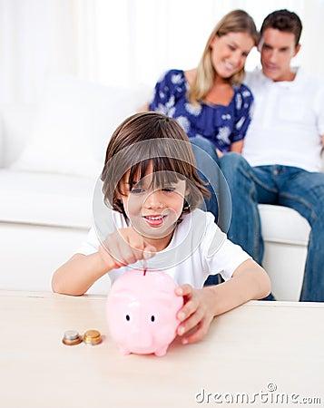 Joyful little boy inserting coin in a piggybank