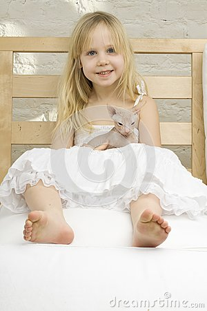 Joyful little girl with kitten