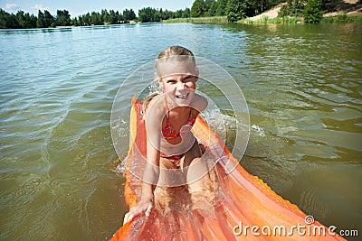 Joyful little girl on mattress in lake