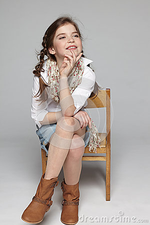 Joyful little girl sitting on the chair