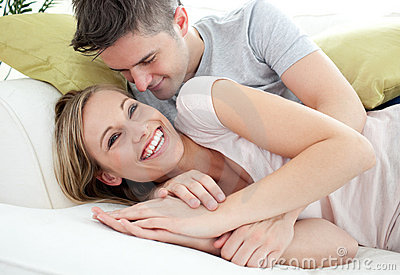 Joyful lovers having fun together on a sofa