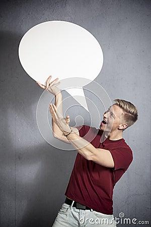 Joyful man presenting white empty speech balloon.