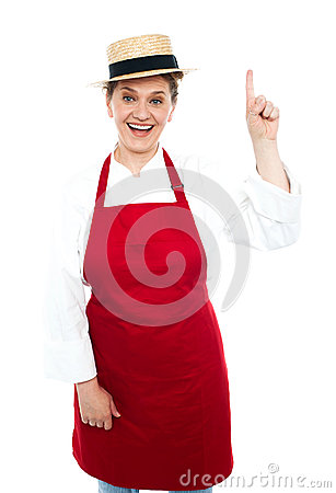 Joyful middle aged cook pointing upwards