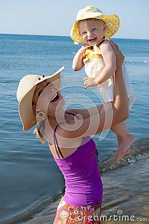 Joyful mother and daughter at beach