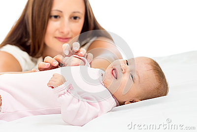 Joyful mother playing with her baby girl