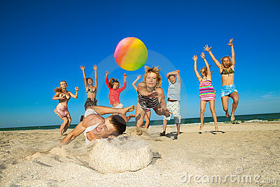 Joyful people playing volleyball