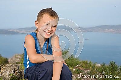 Joyful pojke överst av ett berg