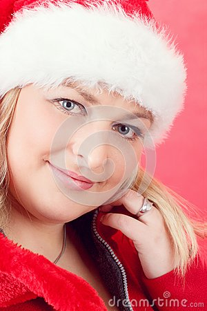 Joyful pretty woman in red santa claus hat smiling
