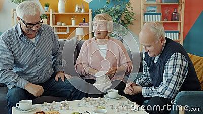 Joyful senior people enjoying lotto game indoors at home talking entertaining. Joyful senior people are enjoying lotto game indoors at home talking entertaining stock video