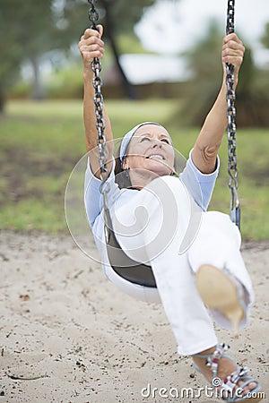 Joyful senior woman on swing active retirement
