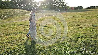 Joyful siblings running through green grassy field stock video