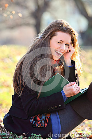 Joyful and smiling girl reading a book in the park