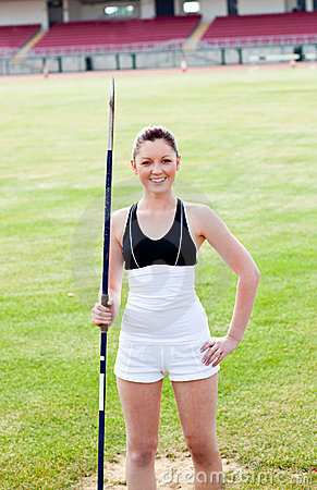 Joyful sporty woman holding a javelin in a stadium