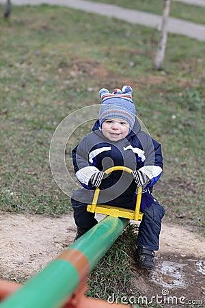 Joyful toddler on seesaw