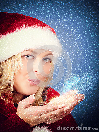 Joyful woman blowing stars in red santa claus hat