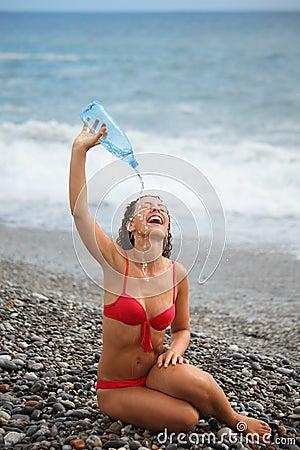 Joyful woman with bottle is sitting on coast