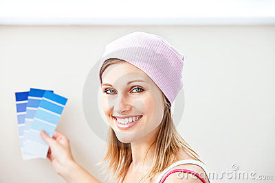Joyful woman choosing color for painting a room