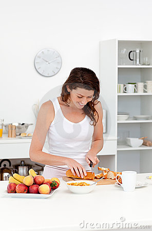 Joyful woman cutting bread for breakfast