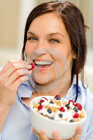 Joyful woman eating cereal in the morning