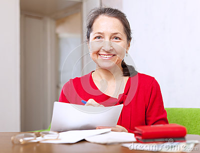 Joyful  woman fills in payment documents