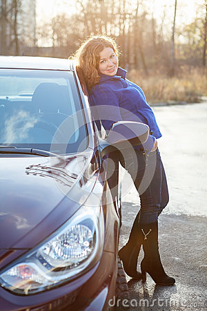 Joyful woman in full length leaned against car