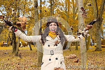 Joyful woman having fun in autumn city park