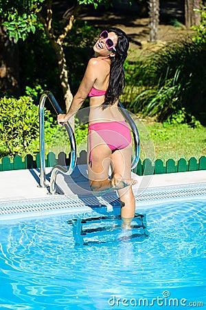 Joyful woman having fun at swimming pool on summer