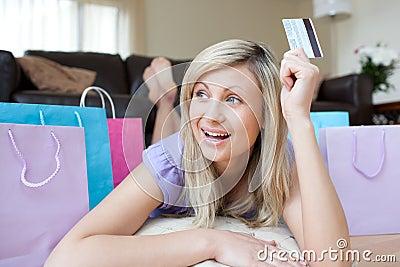 Joyful woman holding a credit card after shopping