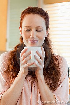 Joyful woman holding a cup of coffee