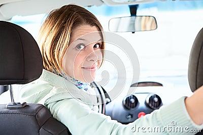 Joyful woman inside of car looking back
