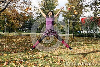 Joyful woman jumping in autumn park