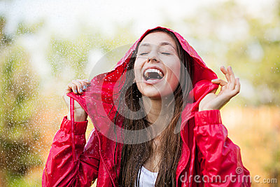 Joyful woman playing in rain