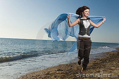 Joyful woman running at sea shore