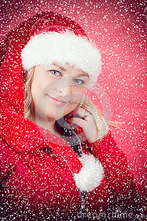 Joyful woman in santa claus hat with snowflakes