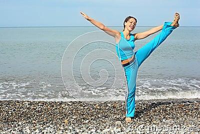 Joyful woman stretching on sea coast