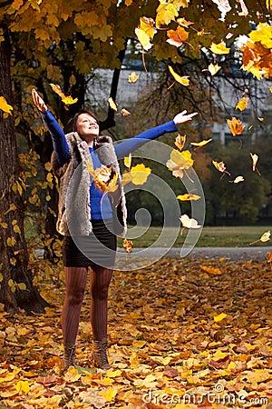 Joyful woman throwing autumn leaves
