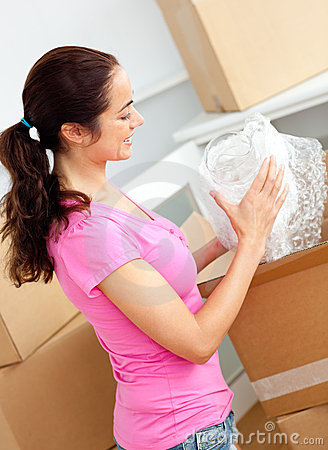 Joyful woman unpacking boxes with glasses