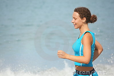 Joyful woman wearing sporty clothers is running.