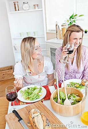 Joyful women having fun while eating salad