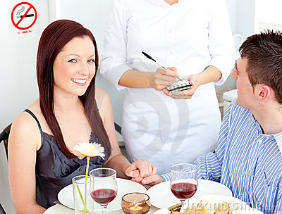 Joyful young couple dining at the restaurant