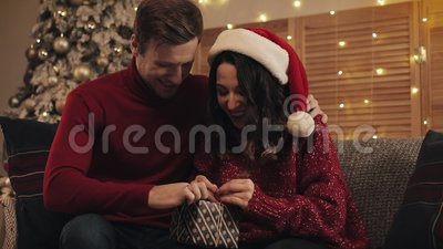 Joyful Young Couple in Love Finalize Christmas Gift Bandaging Tape i przywiązany w kłębie siedząc na sofie w pobliżu Bożego Narod zbiory wideo