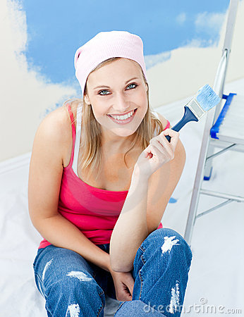 Joyful young woman holding a paint brush smiling