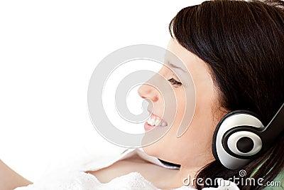 Joyful young woman listening music with headphones