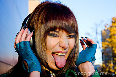 Joyful young woman listening music in headphones