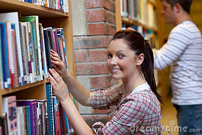 Joyful young woman looking for a book