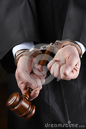 Judge with gavel in handcuffs