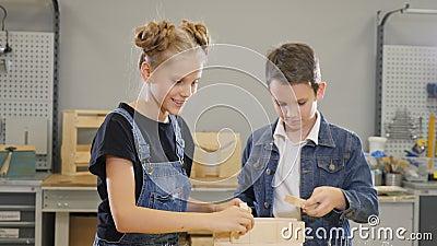 Juego de niños en el taller del arte Niño pequeño lindo y su hermana escuela-envejecida que juegan con los pedazos semielaborados almacen de metraje de vídeo