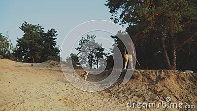 Juego feliz de la mujer joven con su perro mixbreed en el bosque del pino cerca del río grande almacen de video