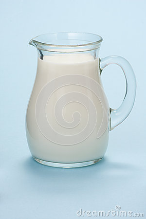 Jug with fresh milk on a blue