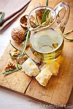 Jug of olive oil, Grana Padano cheese and walnuts